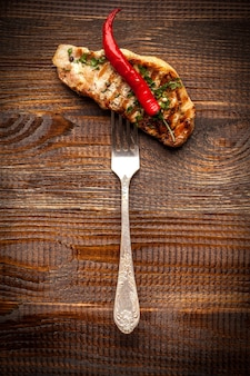 グリルされた肉。揚げたステーキは鋳鉄製のフライパンの上に横たわり、グリル、野菜のグリル、玉ねぎ、チェリートマト、マッシュルーム、赤唐辛子を焼きます。レストランの美しい料理。