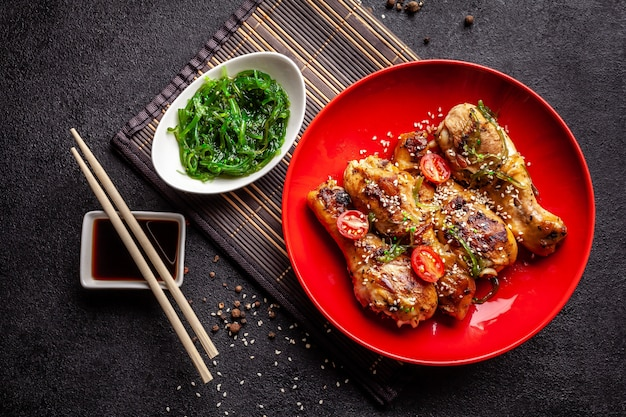 Жареные куриные ножки с острым перцем, кунжутом, салатом чука, китайским горошком на черном столе.