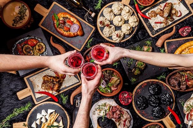 Грузинская кухня. большой накрытый стол из разных блюд для всей семьи на выходных. кебаб, лула, лаваш, сыр сулугуни, хачипури, хинкали. фоновое изображение, вид сверху