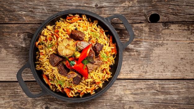 木製テーブルの上に鋳鉄のフライパンで肉と国立ウズベキスタンのピラフ。