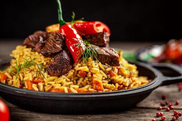 オリエンタル料理のコンセプト。木製テーブルの上に鋳鉄のフライパンで肉と国立ウズベキスタンのピラフ。背景画像。平面図、コピースペース、フラットレイアウト