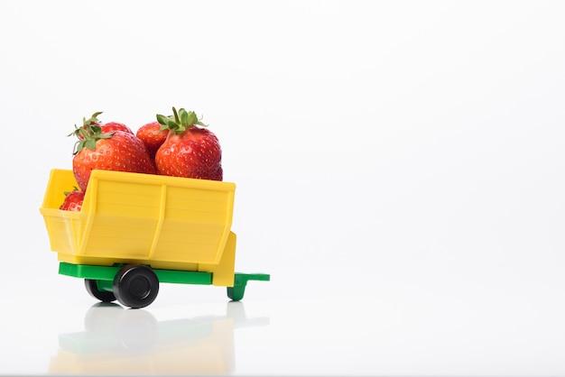 Доставка экологически чистой клубники из сада. свежая клубника от производителя. доставка свежей органической клубники в срок. изолированные на белой стене.