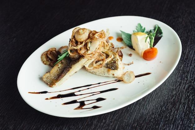 木製テーブルの上の白い皿にタマネギのグリルサバ