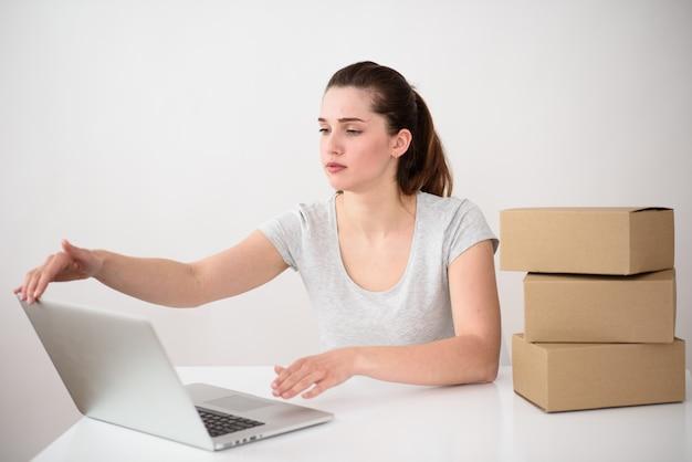 Девушка собирается закрыть крышку ноутбука. рядом стопка картонных коробок на столе. конец рабочего дня.