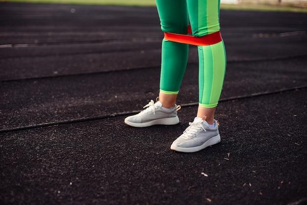 Ноги девушки в светло-зеленых леггинсах с розовой резинкой для тренировки на стадионе