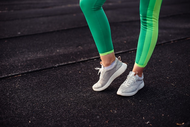 Ноги девушки в светло-зеленых леггинсах на тренировке на стадионе, на улице. ноги согреют