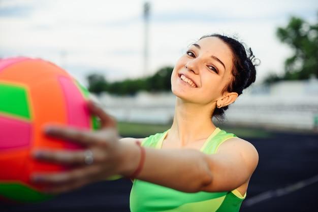 スタジアムで筋肉がうごめく美しい巻き毛の女の子。ボールでウォームアップ。女の子はスポーツに行きます。ライトグリーンのトラックスーツ。