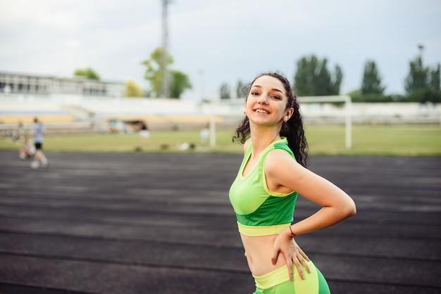 スタジアムで筋肉がうごめく美しい巻き毛の女の子。女の子はスポーツに行きます。薄緑色のトラックスーツ