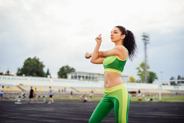 縮れ毛のブルネットは、スタジアムでスポーツをします。ストレッチ、手をウォーミングアップ、運動をしている女の子