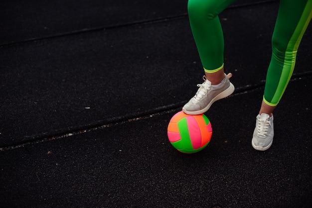 Ноги девушки в светло-зеленых леггинсах на ярком мяче, тренировка на стадионе, на улице. ноги согреют