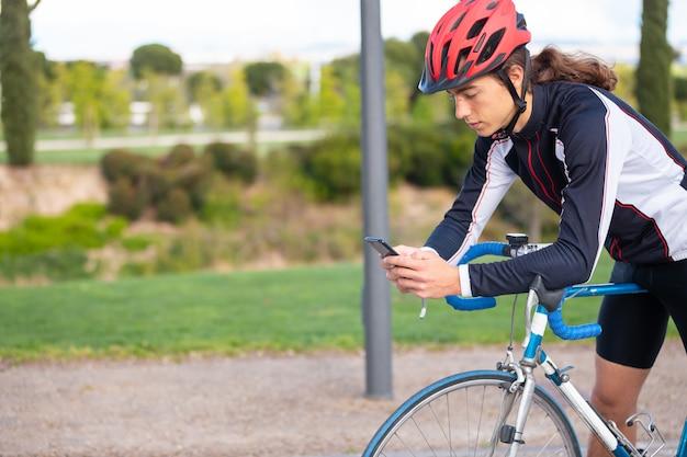 公園でサイクリング後リラックスしながらスマートフォンを使用してスポーツウェアとヘルメットで若い疲れたクールな男性サイクリスト