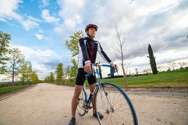 ヘルメットとスポーツウェアの距離を見て、曇り空を背景に自転車で田舎道に立っている間無限を考える若い男
