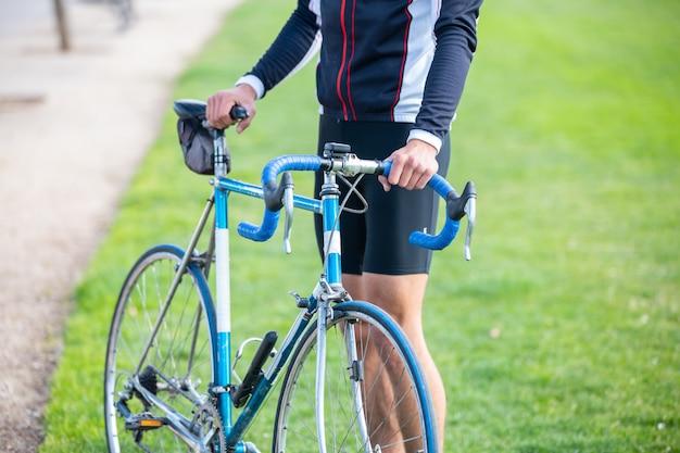 公園で自転車に座っているスポーツウェアで認識できない若者に合う男性サイクリスト