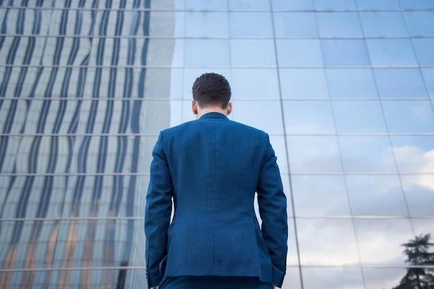 ガラスの建物の背景にポケットに手で立っている上品なスーツのビジネスマンの背面図。