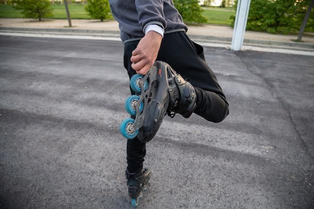 公園内の道路に手でローラースケートを保持しているスポーツウェアでクールな若者の背面をトリミングします。