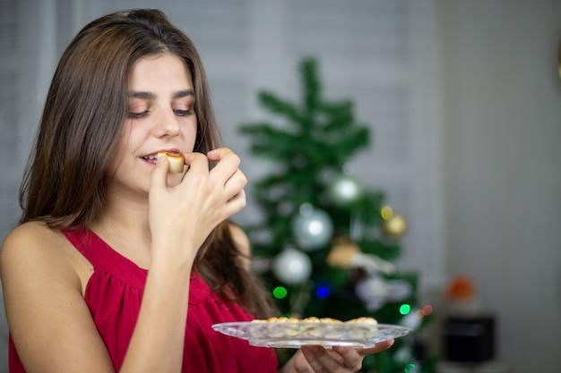 おいしいマジパンのお菓子とプレートを保持しているとクリスマスに食べる女性
