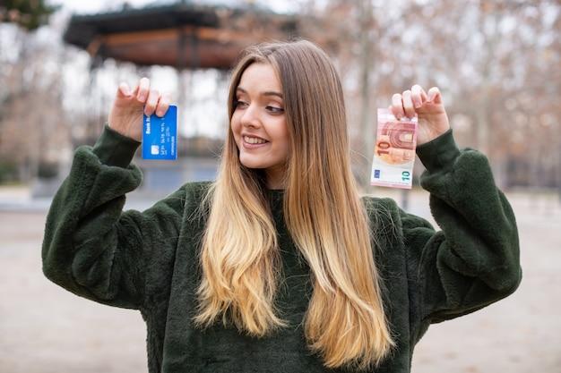 公園に立っている間カメラにプラスチックカードと現金を示す若い女性