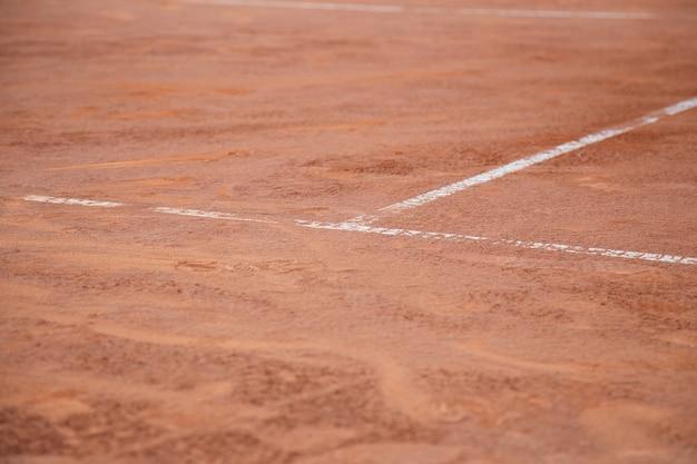 日光の下で白い線でテニスコートの地面。