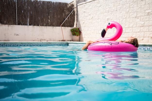 夏休みの晴れた日に青いプールで膨脹可能なフラミンゴに浮かんでいる若い男