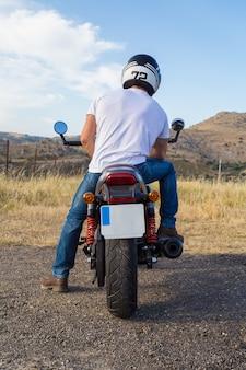 Задний взгляд велосипедиста в шлеме сидя на мотоцикле в горной области.
