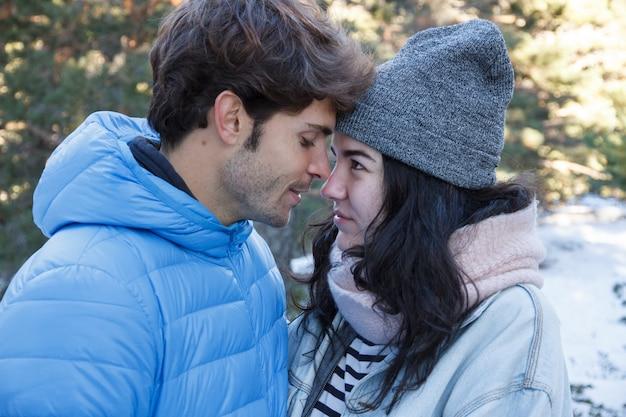 若いカップルが雪の日に山でキスします。