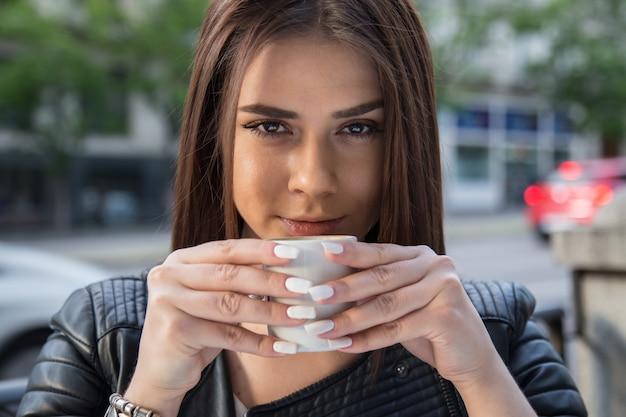 Портрет довольно кавказской женщины, пить кофе на террасе на улице.