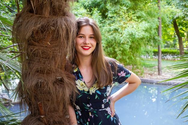 夕暮れ時、パラディシア公園でポーズをとってスタイリッシュな服を持つ若い女性