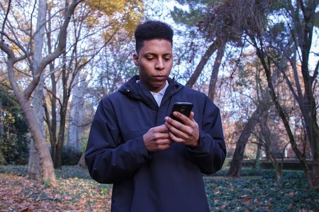 Чернокожий человек отправляя сообщения с его умным телефоном в поле.