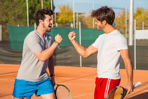 Двое друзей стоят на теннисном корте и подбадривают друг друга перед матчем.
