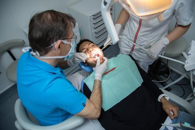 アシスタントと歯科医院で働いている若いアフリカ系アメリカ人男性の口腔を調べる男。