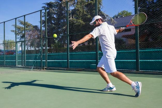 Профессиональный теннисист играет на теннисном корте.