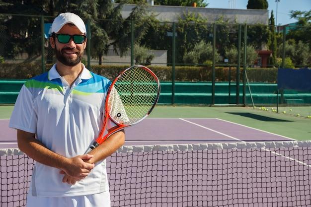 テニスコートで彼の学校を歓迎するテニス教師