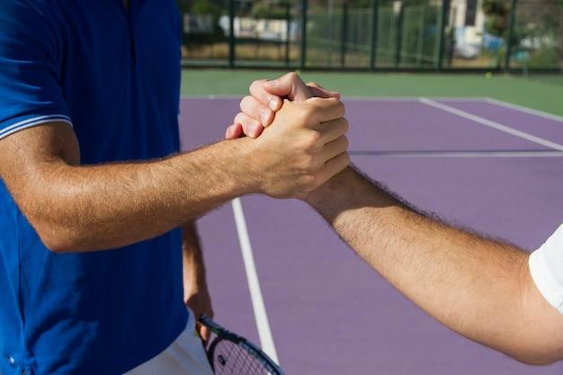 Двое мужчин, профессиональные теннисисты, пожимают друг другу руки до и после теннисного матча