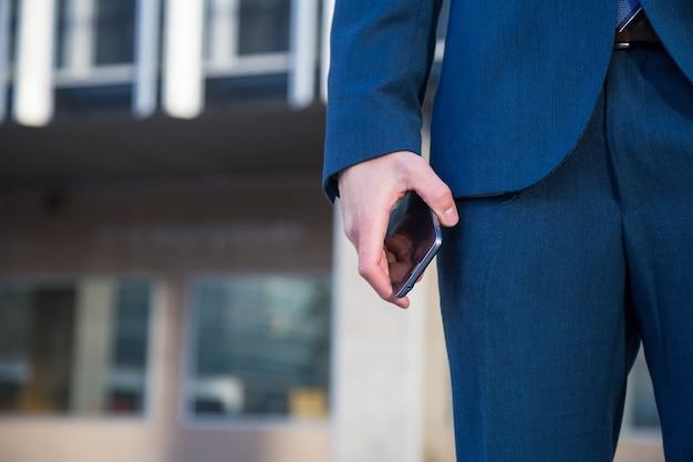 路上のポケットに手で立っている間携帯電話を保持しているトレンディなスーツを着た男の顔のないショット。