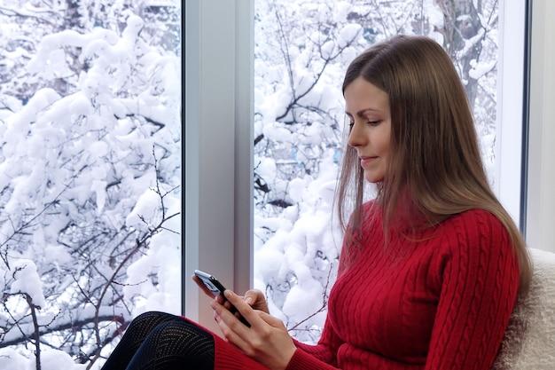 Красивая девушка сидит на подоконнике с помощью смартфона. зима на улице.