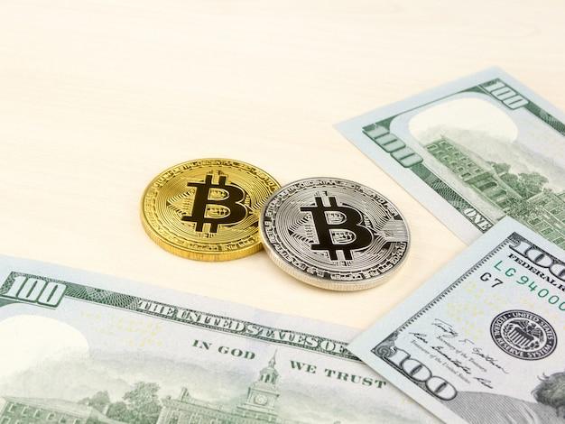 Золотая и серебряная монета биткойна на долларах сша закрывает вверх.