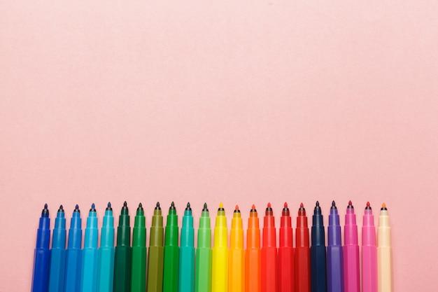 Ассортимент красочных фломастеров на пастельно-розовом