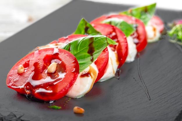 モッツァレラチーズとトマトの暗いプレート上の新鮮なイタリアのカプレーゼサラダ