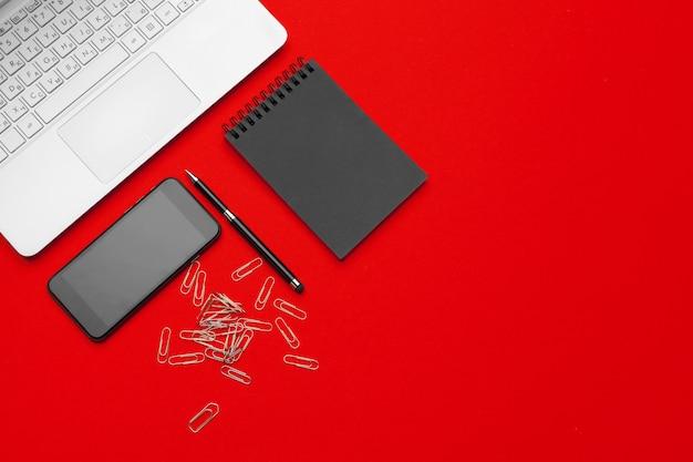 Стол офисный стол с канцелярских принадлежностей на красном фоне