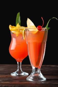Алкогольные и безалкогольные коктейли на деревянный стол. летние холодные напитки