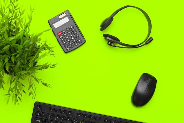 事務用品と緑の背景のひな形のトップビュー