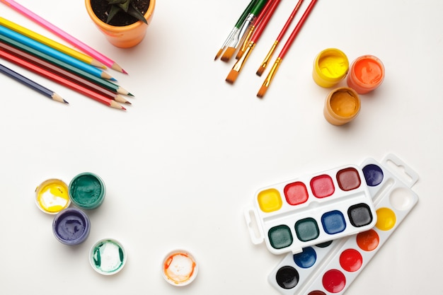 水彩画用品、ブラシ、カラフルな鉛筆の平面図。水彩画の作成プロセス。コピースペース。