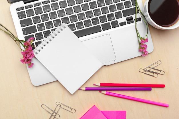 定型化された女性のオフィスデスク。ワークスペース、ノートパソコン、フラワーブランチ、コーヒーカップ