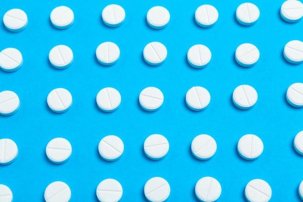 無秩序に散らばった白い錠剤パターン。