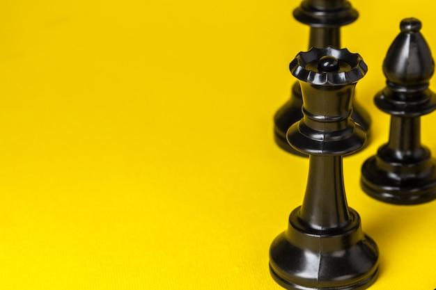 Шахматные фигуры на желтом фоне вид сверху копией пространства
