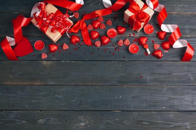Подарочная коробка с красными сердцами на фоне деревянный стол