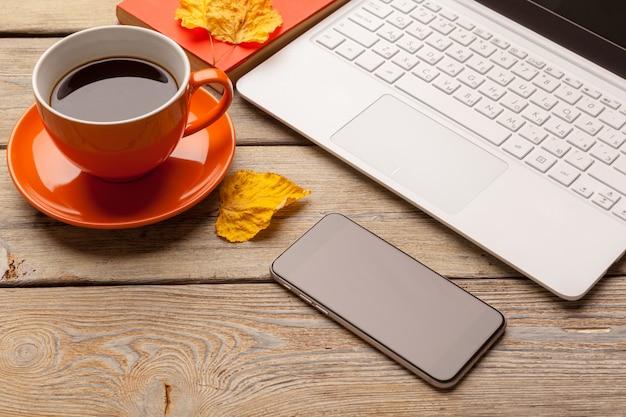 木製テーブルの上のオレンジ色のプレートにコーヒーカップ。オフィスインテリア