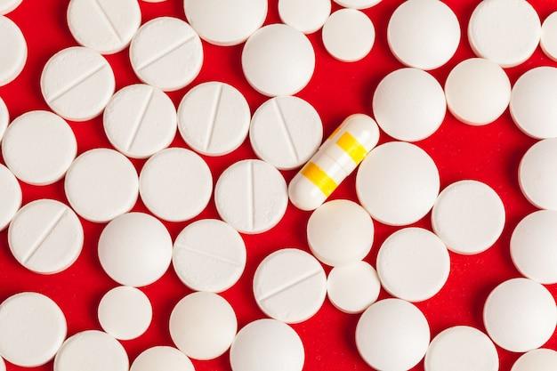 Многие таблетки крупным планом на красном фоне