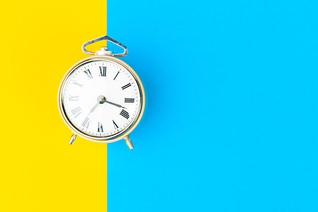 Черный будильник на цветном блоке желто-синий фон