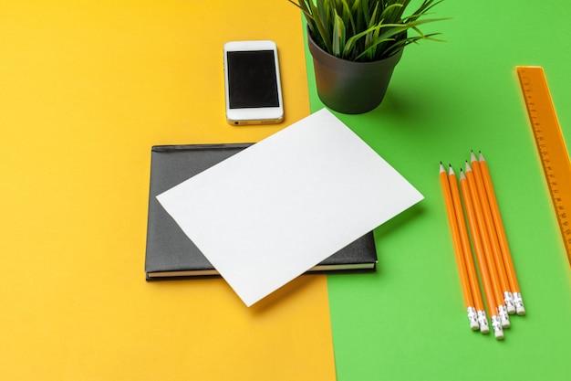 机の上のスマートフォンで空白の紙。トップビュー、フラットレイアウト